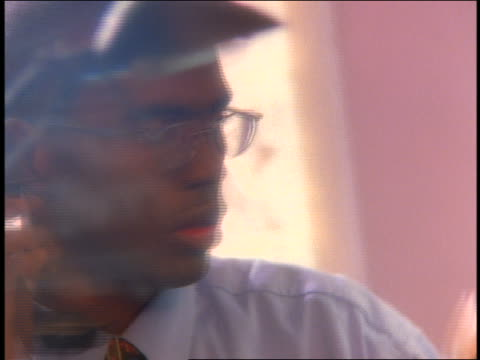 close up moving filter over face of stressed Black businessman arguing on telephone + looking at watch