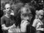 B/W 1967 close up mustached male hippie in eyeglasses smoking joint outdoors at bein / London / newsreel