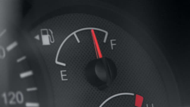 Close up needle on car fuel gauge moving from empty to full and back again