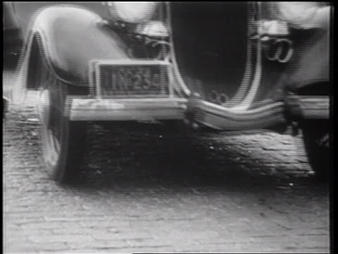 B/W 1939 close up NY license plate of car stopping in front of camera / documentary
