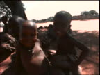 close up of 3 Ndebele children smiling at camera outdoors / they run away / South Africa