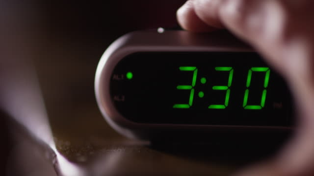 Close up of a digital alarm clock which reads 3:30 a.m. and a man's hand shuts of the alarm.