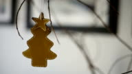 Close up of a handmade cardboard pine tree ornament with a star on the top hanging from a branch.