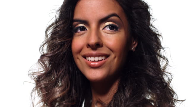 Close up of a hispanic woman smiling looking into camera.