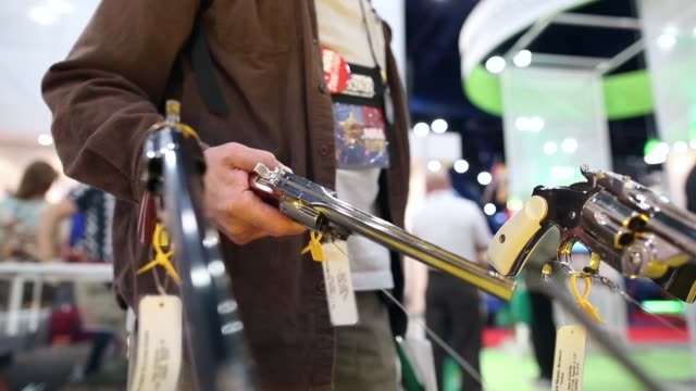 Close up of a man trying out a revolver during the 2013 NRA Annual Meeting and Exhibits at the George R Brown Convention Center on May 4 2013 in...