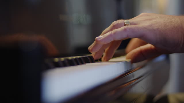 Close up of a man's fingers tickling the ivory keyboard of a piano.
