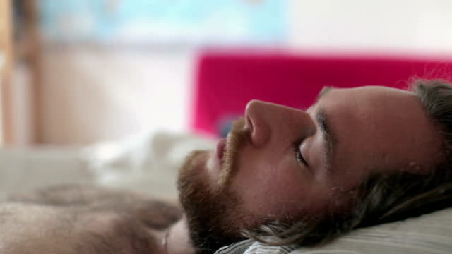 Close up of a sleeping man waking up