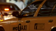 Close up of a taxi driver getting into a cab and beginning to drive off