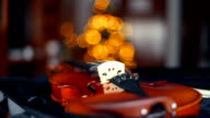 Close up of a violin with bokeh of Christmas lights in the background.