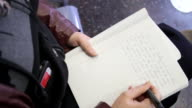A close up of a woman's hands while she writes in her journal.