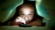 Close up of a young girl playing game under blanket