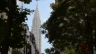 Close up of an American Flag waving over the streets of New York City with the top of the Chrysler building slowly revealed behind it Close up shot...