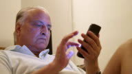Close up of an Indian man using the touch screen on his smartphone device sitting on a couch in his living room