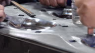 Close up of asian worker Polishing front metal mold. Dolly shot.