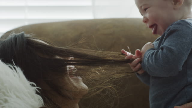 Close up of baby son pulling hair of mother on sofa / Provo, Utah, United States