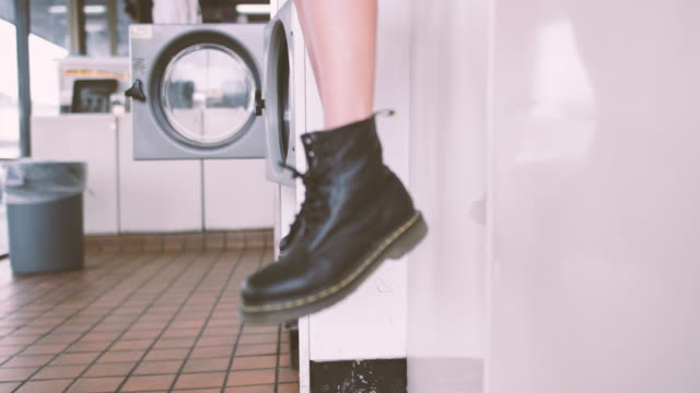 Close up of boots of female sitting waiting in laundrette