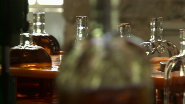 Close up of bottles of bourbon moving through machines in bottling plant.