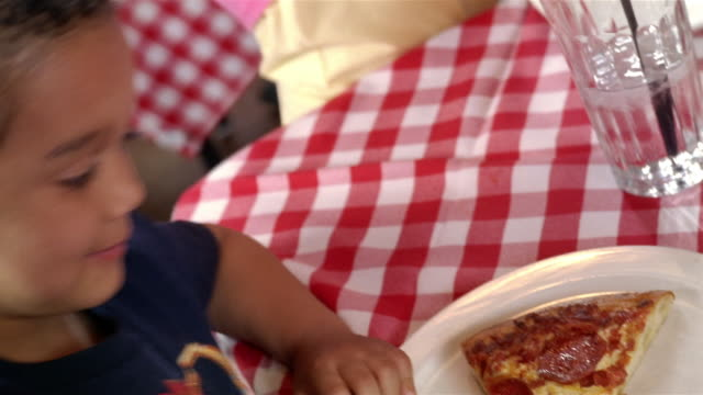 Close up of boy smiling up at camera at pizza restaurant / holding slice of pizza up for camera