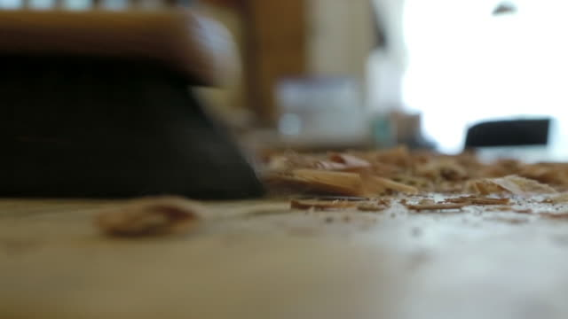 Close up of brush sweeping wood shavings and sawdust off table