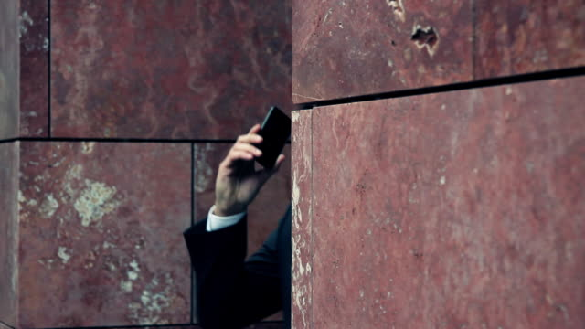 Close up of Business man leaving office and answering phone call