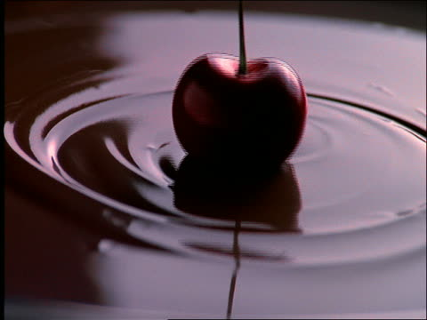 close up of cherry being dipped into chocolate sauce
