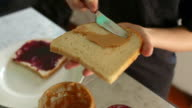 Close up of child making peanut butter and jelly sandwich