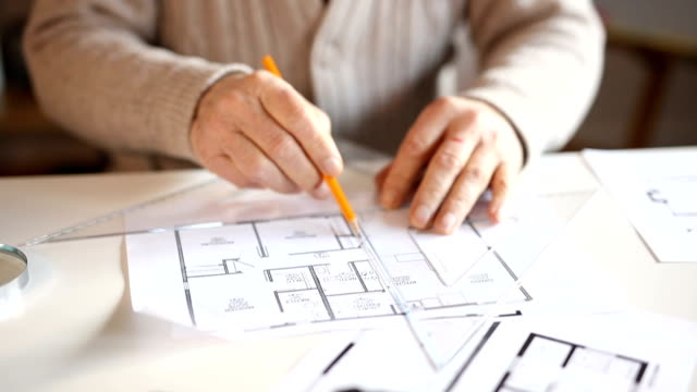 Close up of elderly man's hands drawing on blueprints