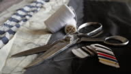 A close up of fabric and tools of a fashion designer