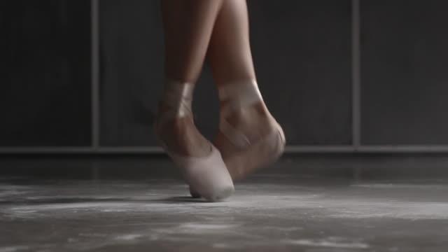 Close up of female ballerina's shoes performing brisé, échappé, entrechat