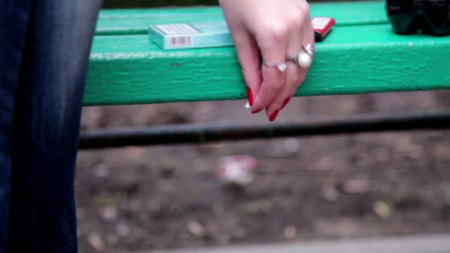 Close up of female hand sticking chewing gum under the park bench