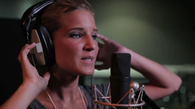 Close up of female singing in recording studio