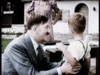 Close up of front page photograph of Hitler / Adolf Hitler takes his own life on April 30 1945 / Footage of Hitler's life / Hitler kneeling talking...