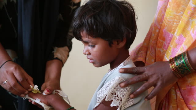 Close up of girl getting plaster/band-aid on her hand in Health Center near Pannur, India