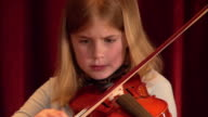 Close up of girl playing violin in music class / pan to boy playing violin / Los Angeles, California