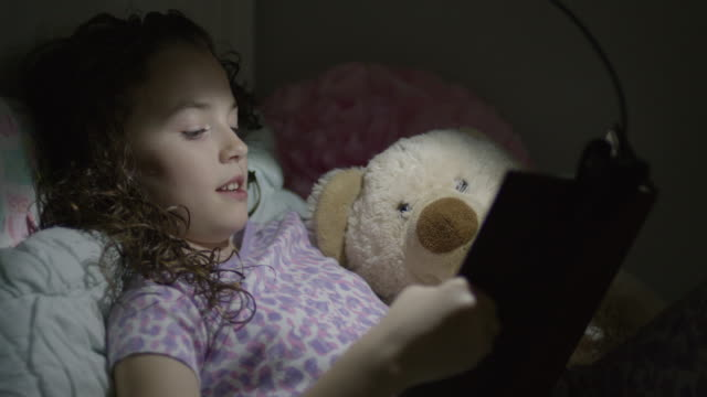 Close up of girl reading book in bed at night / Provo, Utah, United States