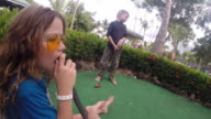 Close up of girl with yellow sunglasses holding golf club and father and son getting ready to take next shot at mini golf at resort.