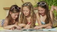 Close up of girls reading magazine at poolside / Cedar Hills, Utah, United States