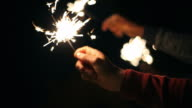 Close up of hand holding sparkler
