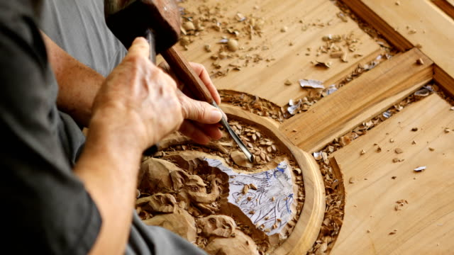 Close up of Hand of carver carving wood