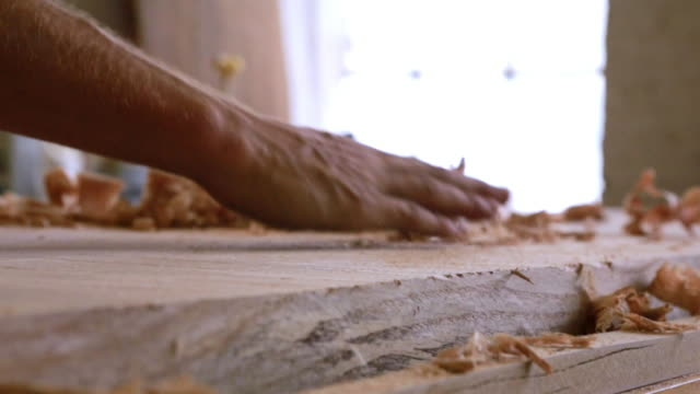 Close up of hand sweeping shavings off block of wood