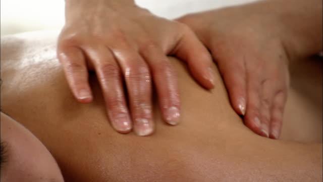 Close up of hands of massage therapist massaging woman's shoulder