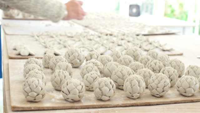 Närbild på händerna att placera och att ordna fina handgjorda porslin prydnadssaker