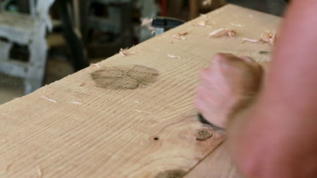 Close up of hands planing block of wood