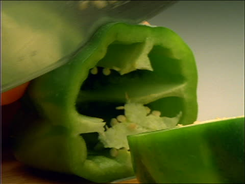 close up of hands slicing green peppers with knife