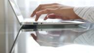 Primo piano di mano di Giovane donna digitando su un portatile con riflesso sulla scrivania, 4 k (UHD)