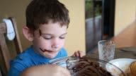 Close up of little boy mixing chocolate and taste testing then falling back in his chair.