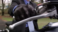 Close up of male professional wearing leather gloves starting motorcycle to go to work