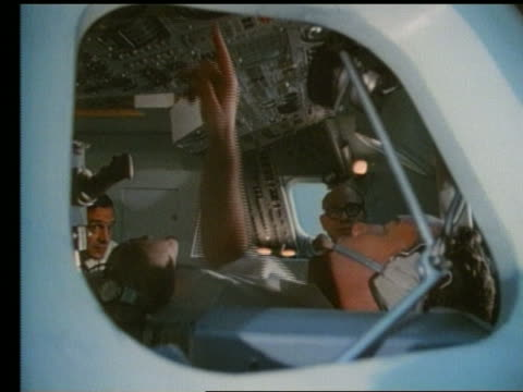 close up of man at controls in space capsule