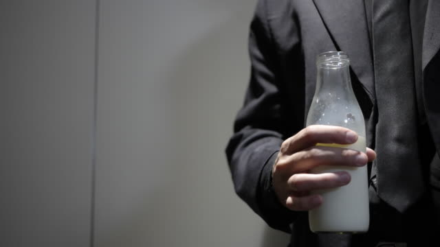 Close up of Man drinking milk from a glass bottle