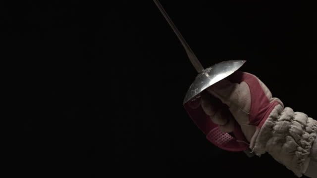 Close up of man holding foil and leaping foward in fencing uniform